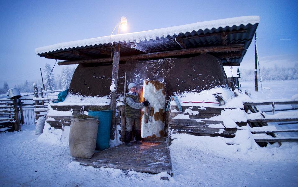 Ein Mann schließt die Türe eines Häuschens im Schnee.