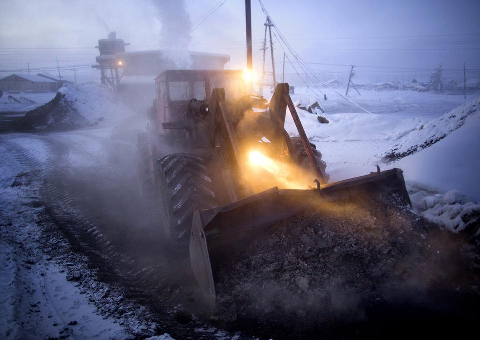 Ein Bagger mit Scheinwerfern im Schnee.