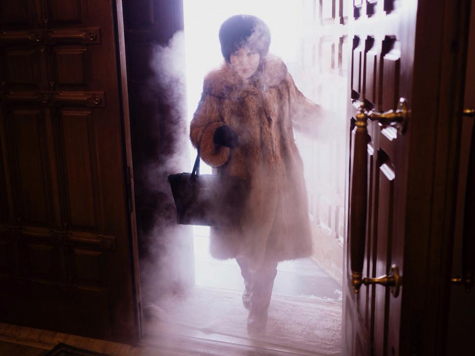 Eine Frau betritt ein Gebäude. Nebel dringt von außen mit ein.