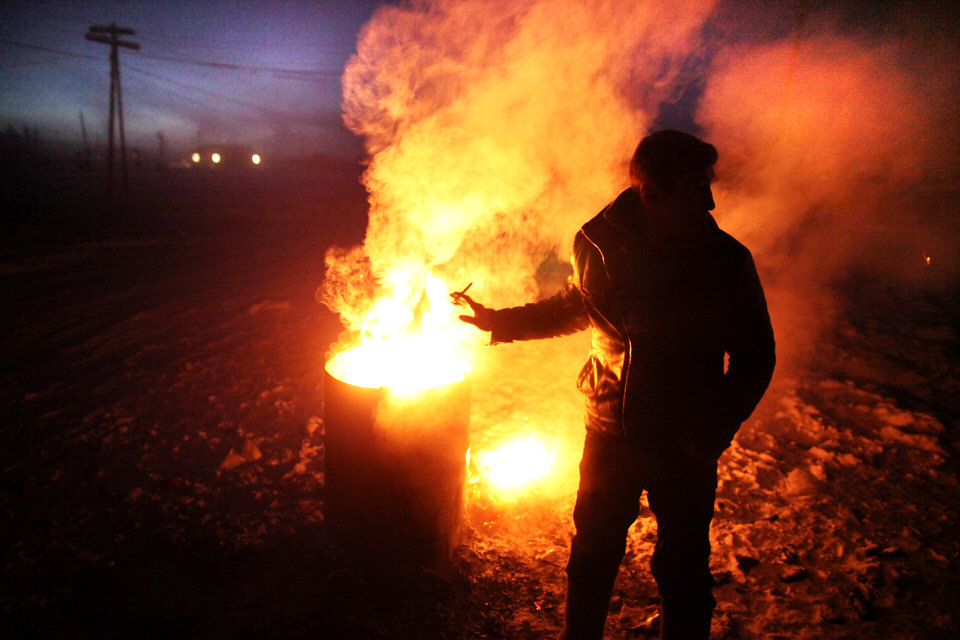 Ein Mann wärmt sich am Feuer aus einer Tonne.