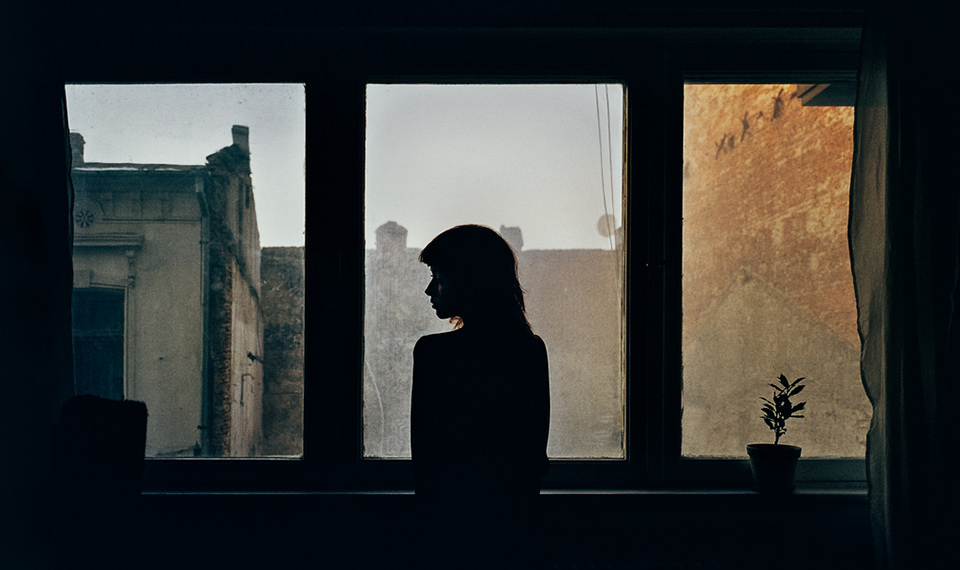 Mädchen im Gegenlicht vor einem Fenster.