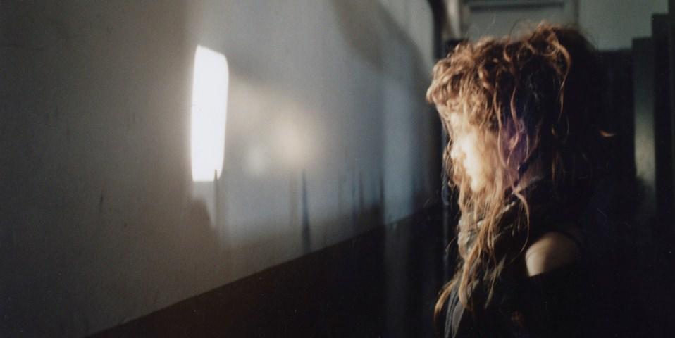 Mädchen steht vor Lichtkegel in Fensterform.