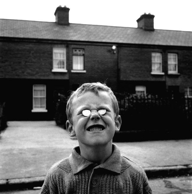 Ein Junge posiert mit zwei Münzen in North Dublins Linenhall Street, 1988.