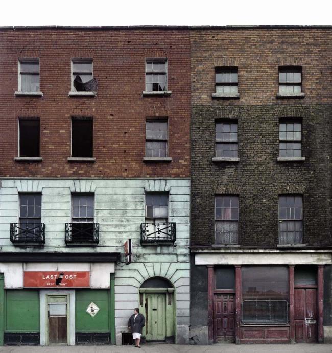 Eine Frau steht vor einem bunten Gebäude.