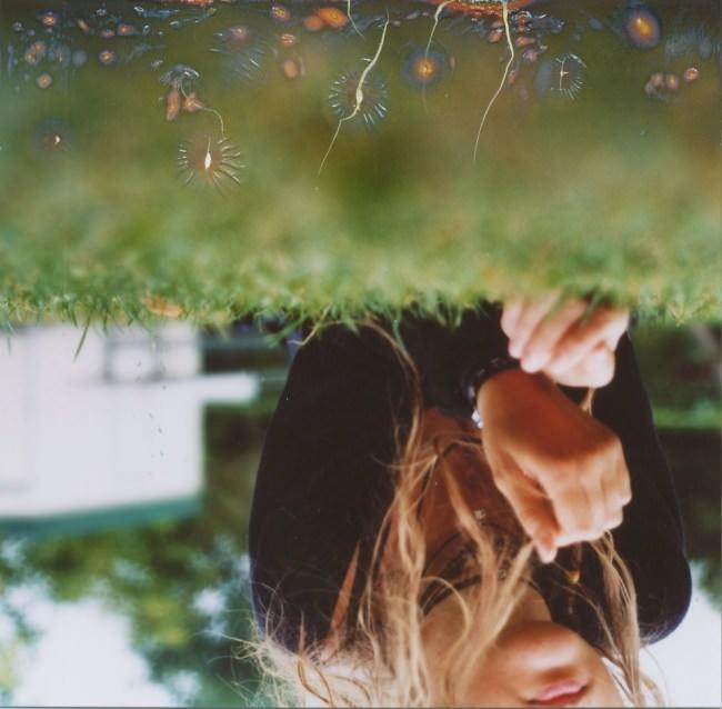 Verkehrt herum stehendes Bild eines Mädchens auf einer Wiese, in die Risse gebrannt wurden.