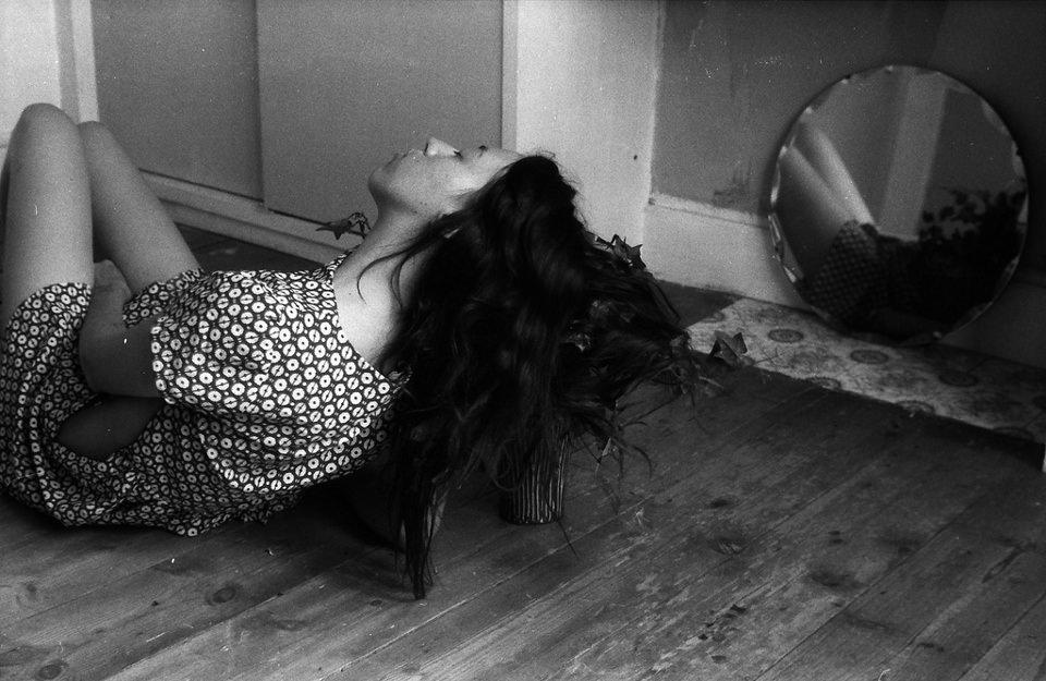 Eine Frau mit offenem Haar liegt vor einem halben Spiegel.