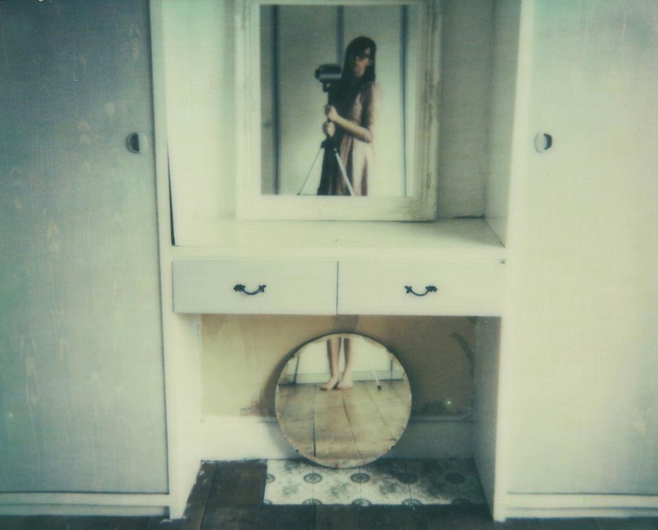 Eine Frau mit Kamera wird durch zwei Spiegel in zwei Hälften geteilt.