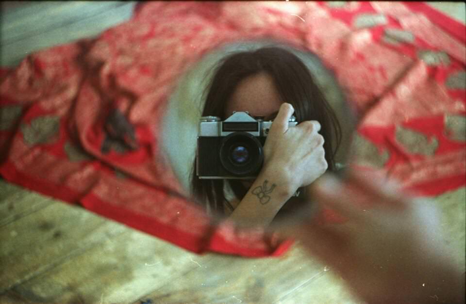 Spiegelbild einer Frau mit Kamera.