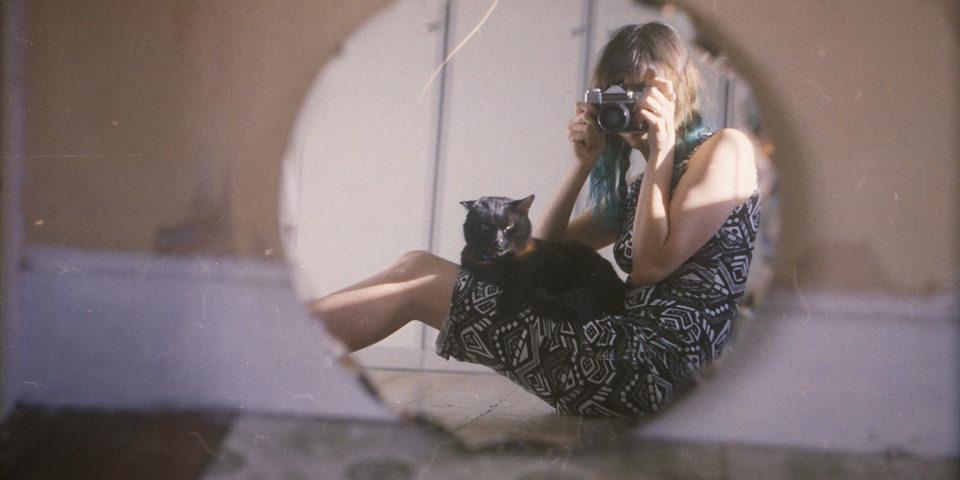 Eine Frau mit schwarzer Katze auf dem Schoss schließt ein Foto in einen Spiegel.