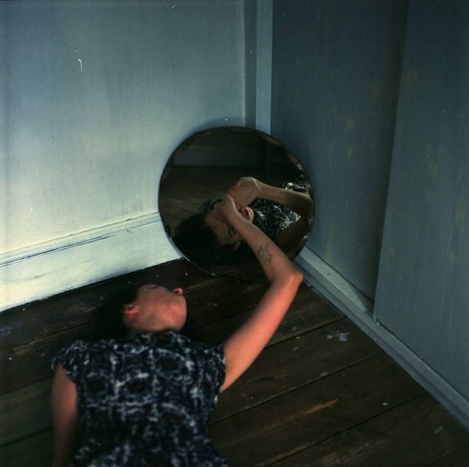 Frau liegt am Boden vor einem Spiegel.