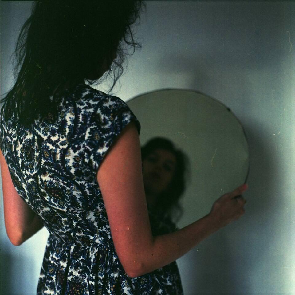Frau hält einen Spiegel in den Händen und schaut hinein.