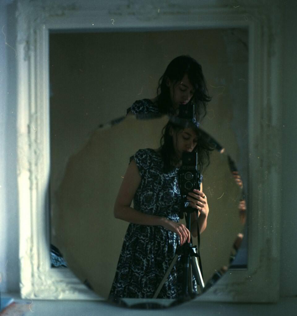 Frau steht mit Kamera vor einem Spiegel.