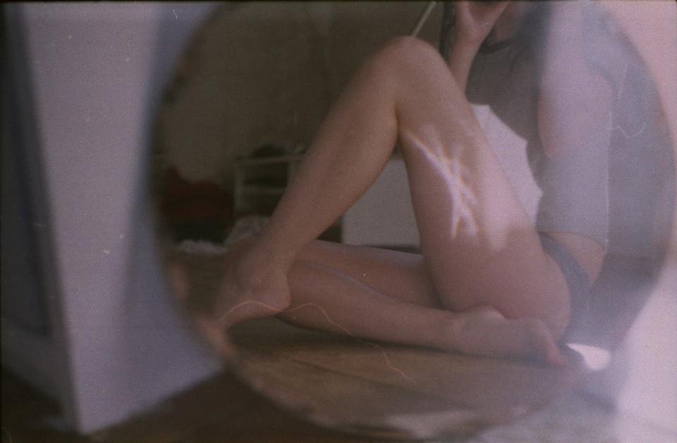 Frauenbeine sind durch einen Spiegel erkennbar.