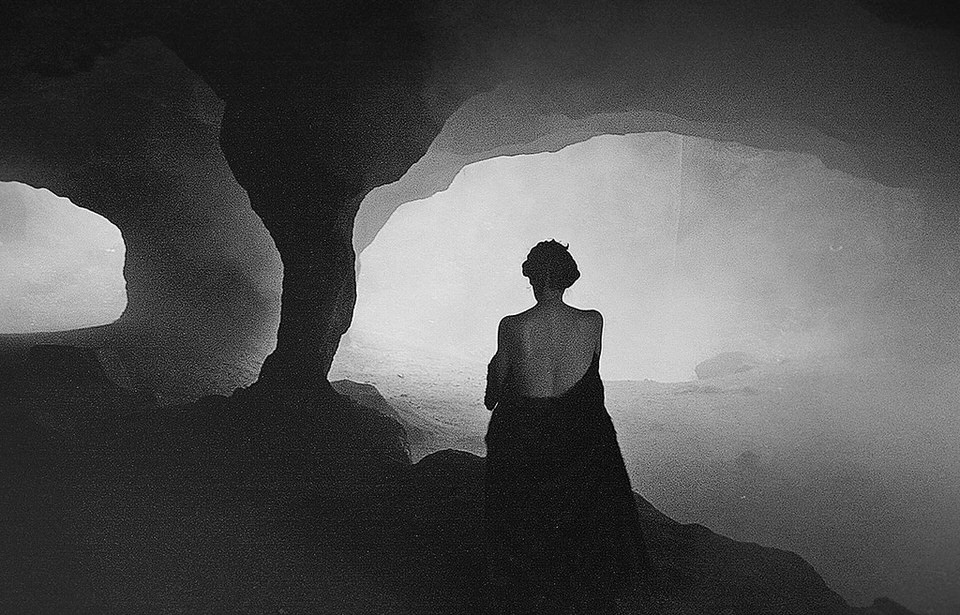 Eine Frau sitzt in einer düsteren Höhle.