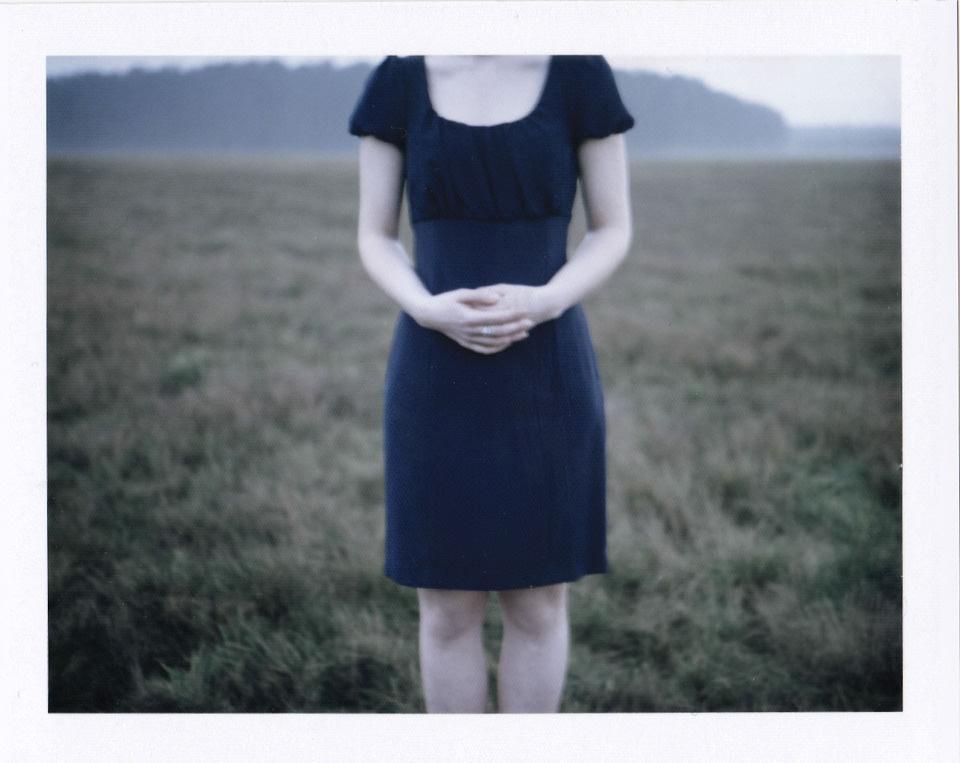 Eine Frau faltet ihre Hände vor ihrem Bauch. Der Kopf ist durch den oberen Bildrand abgeschnitten.