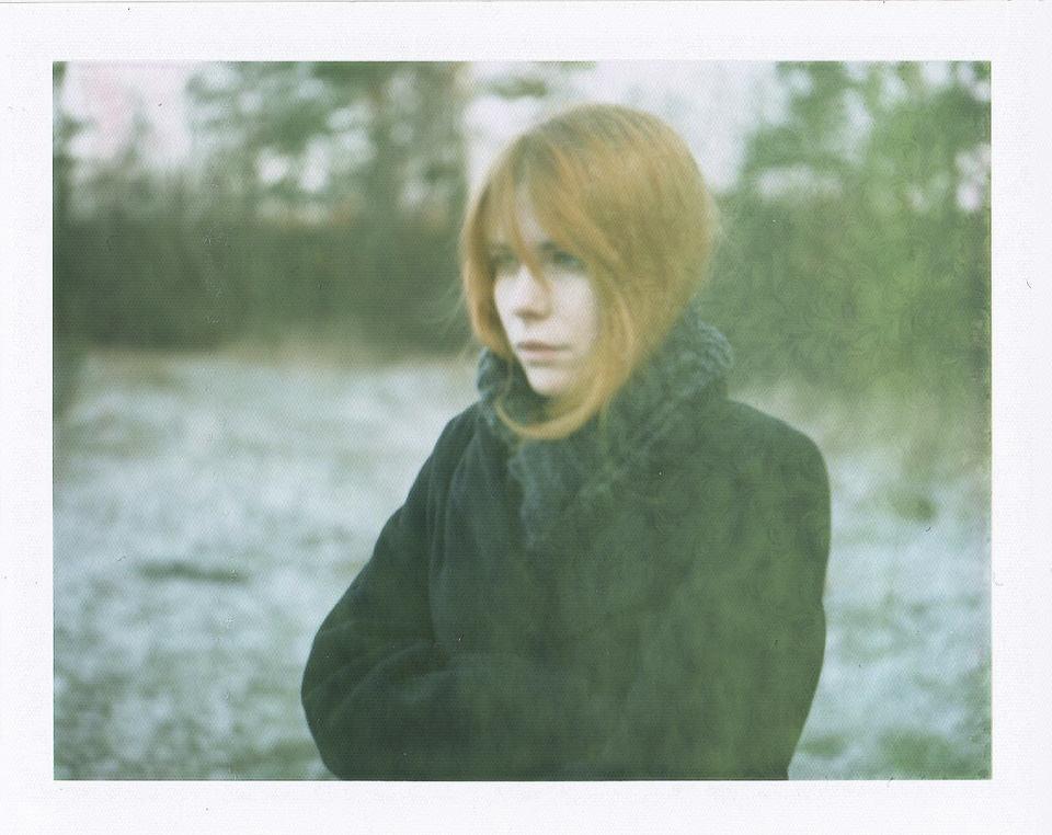 Eine Frau im Mantel vor einer Schneelandschaft.