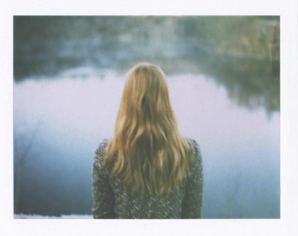 Eine Frau steht mit dem Rücken zur Kamera und sieht in ein Gewässer.