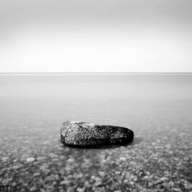 Ein einsamer Stein im flachen Wasser.