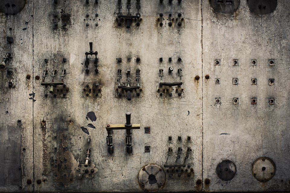 Eine verwitterte Wand mit einigen kaputten Schaltern.