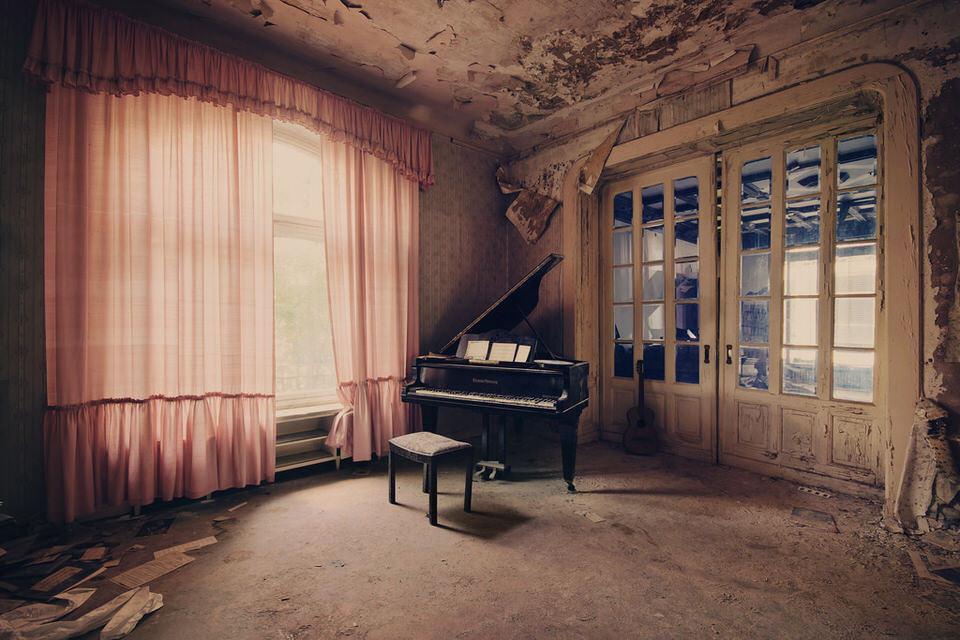 Ein Flügel in einem verfallenen Zimmer mit rosa Vorhängen