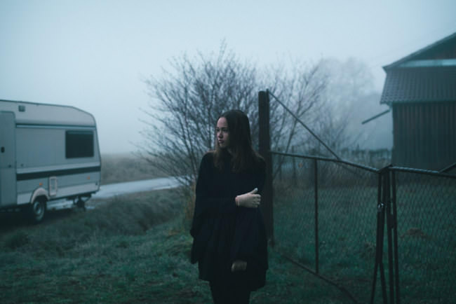 Eine Frau vor einem Zaun