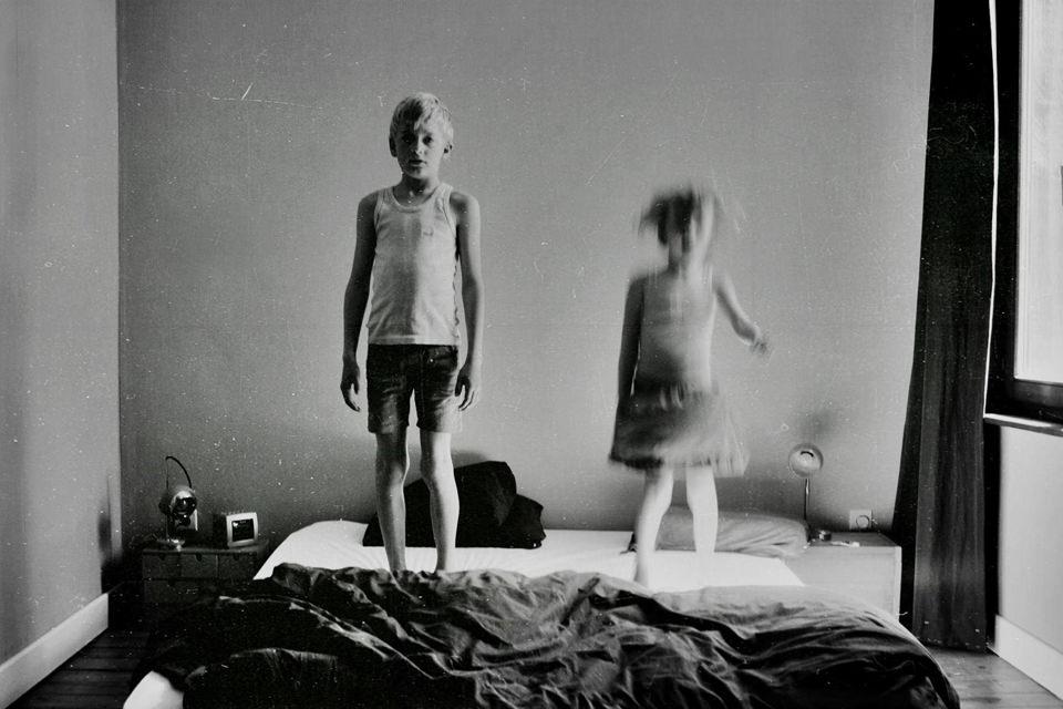 Zwei Kinder hüpfen auf einem Bett.