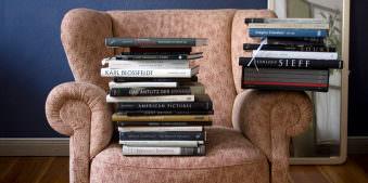 Ein Stapel Foto-Bücher und Bände sitzen auf einem älteren Sessel.