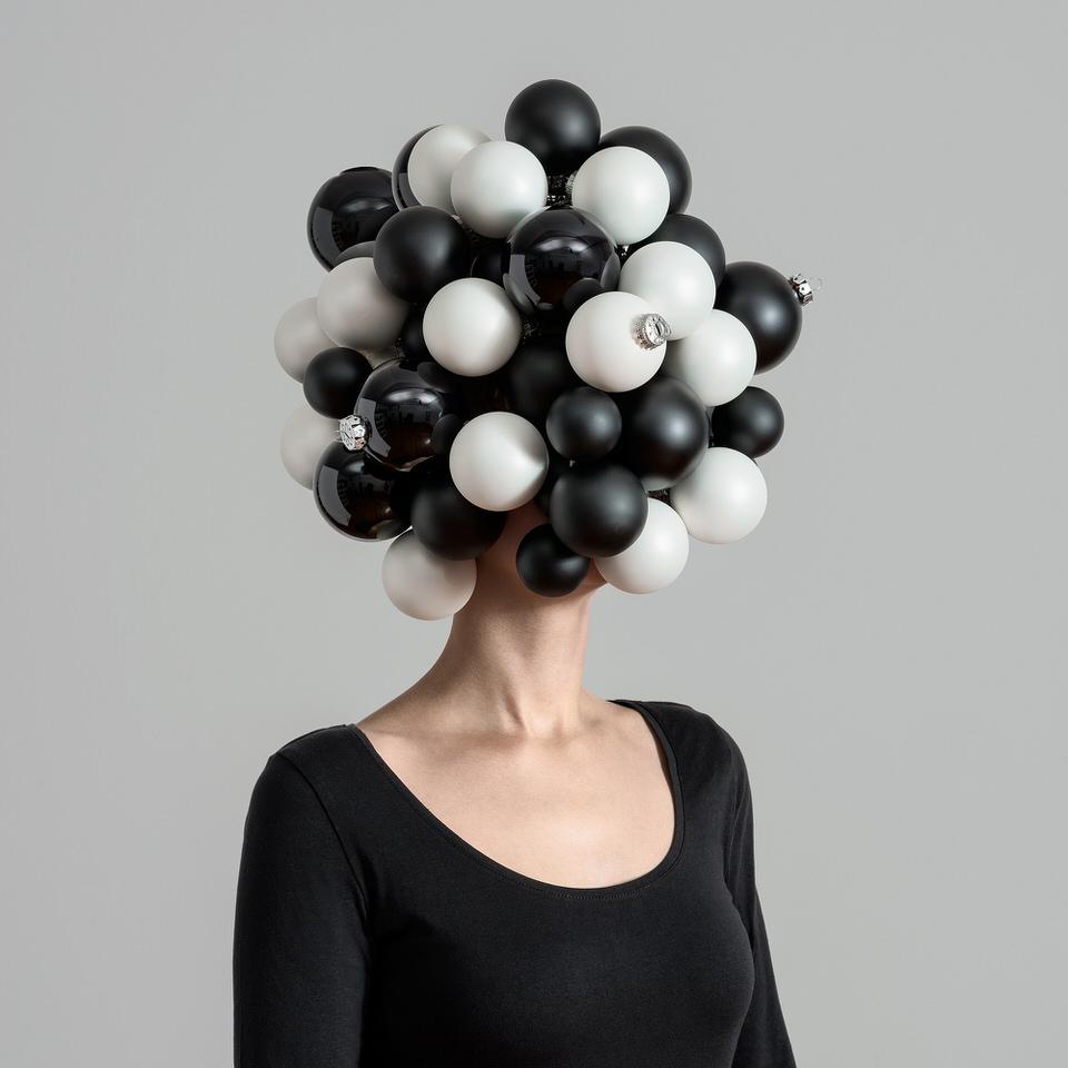 Eine Frau mit Christbaumkugeln auf dem Kopf.