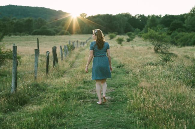 Eine Frau läuft dem Sonnenuntergang entgegen.
