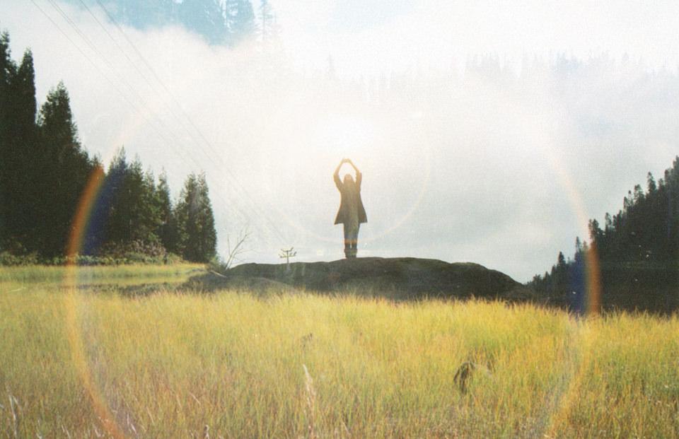 Jemand steht auf einem Hügel und hält die Arme hoch.