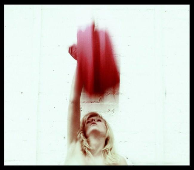 Eine Frau wirft vor einer weißen Wand ein rotes Tuch in die Höhe.