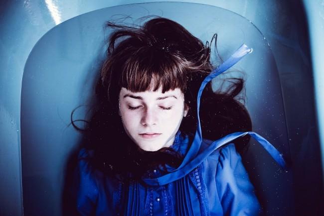 Eine blau gekleidete Frau liegt im Wasser einer blauen Badewanne.