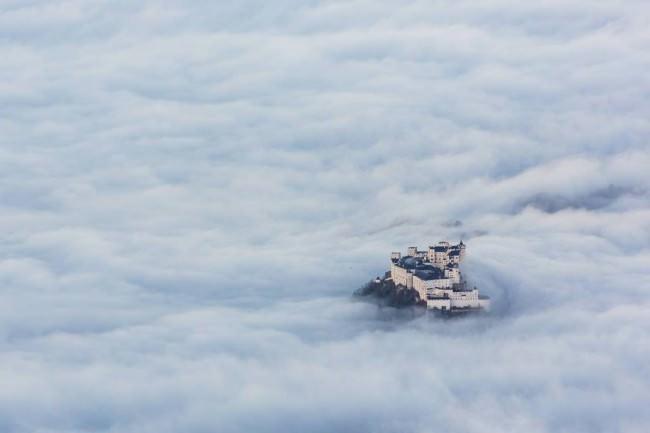 Ein Schloss ragt aus einem Wolkenmeer.