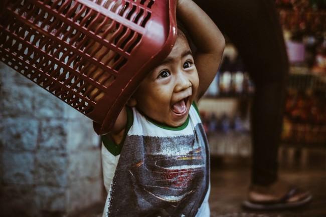 Ein Kind spielt mit einem roten Plastikkorb und freut sich.