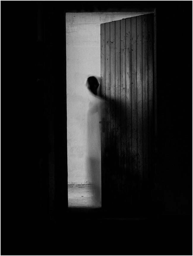 Eine geisterhafte Figur in einer Türöffnung, sonst Dunkelheit.