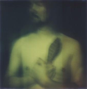 Mann mit Blatt vor der Brust.