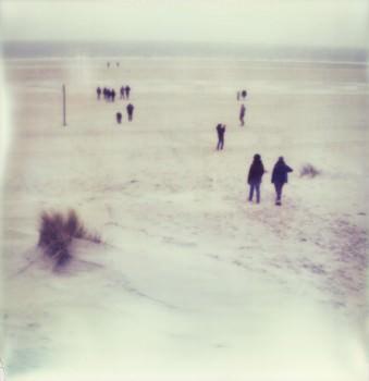 Menschen laufen an einem Strand auf das Meer zu.