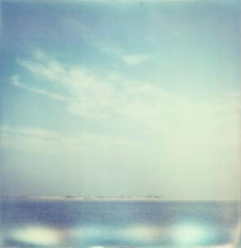 Offenes Meer, am Horizont eine Insel, darüber Wolken am blauen Himmel.