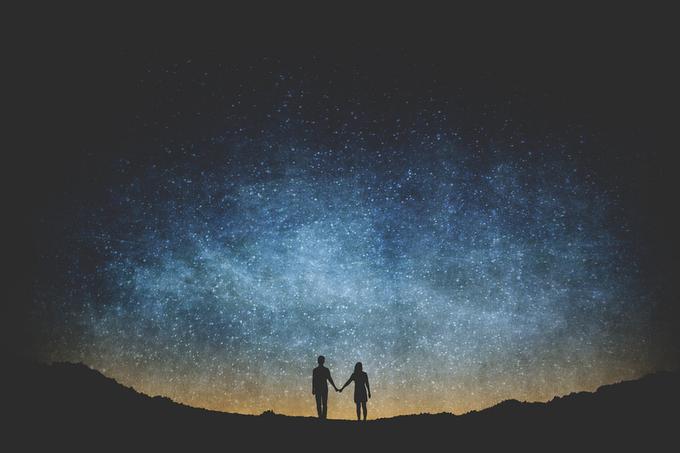 Zwei Menschen unterm Sternenhimmel.