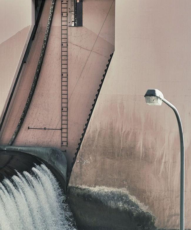 Wasser fließt durch eine Schleuse, an und vor deren Wand eine Leiter und eine Straßenlaterne zu sehen sind.