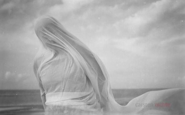 Eine in ein wehendes Tuch gehüllte Person vor Meer und Himmel.
