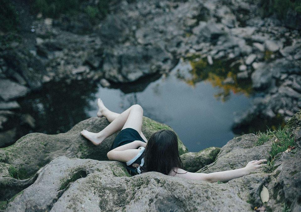 Eine Frau liegt auf einem Felsen. Unter ihr der Abgrund mit See.