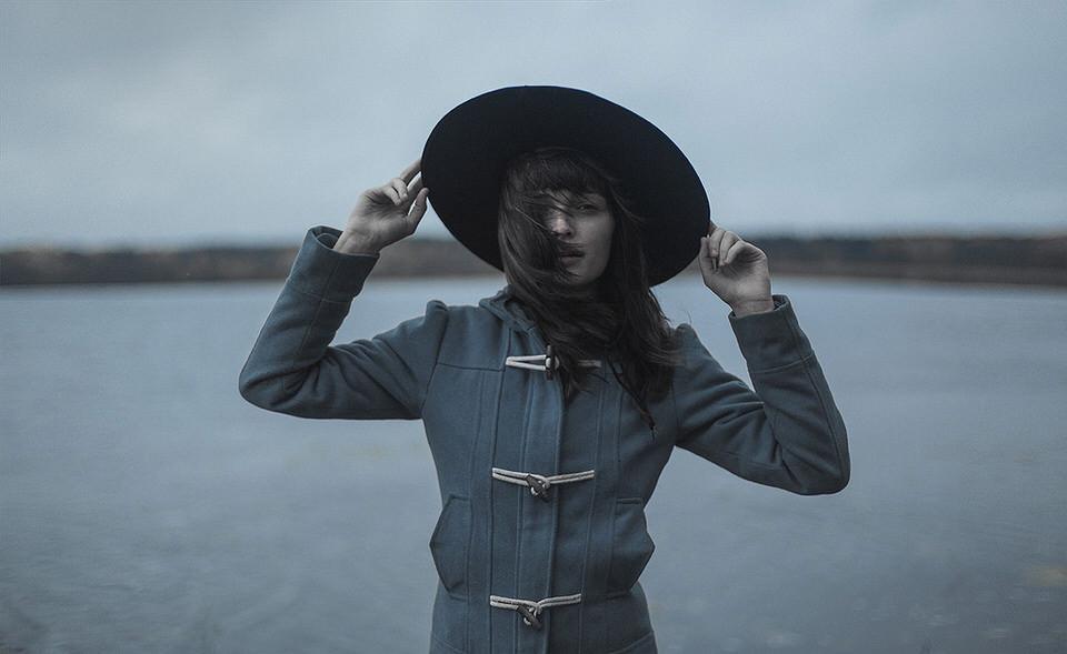 Eine Frau am Wasser hält ihren Hut fest.