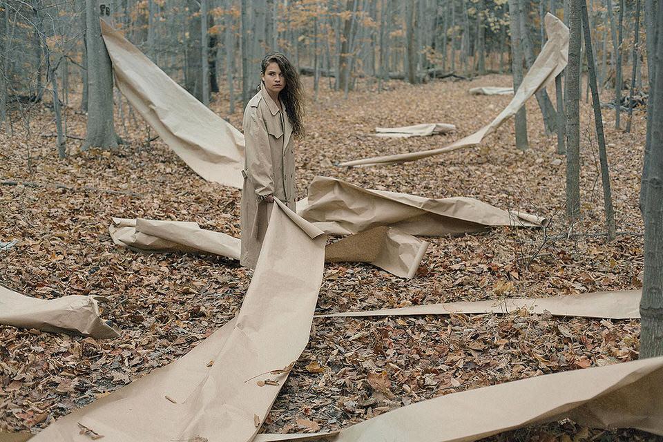 Eine Frau steht mit einer Rolle Papier, die über den Boden ausgebreitet ist, im Wald.