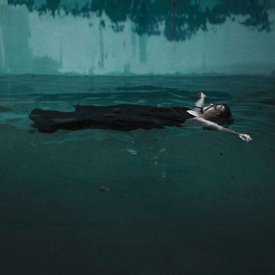 Eine Frau schimmt auf dem Rücken im Wasser.