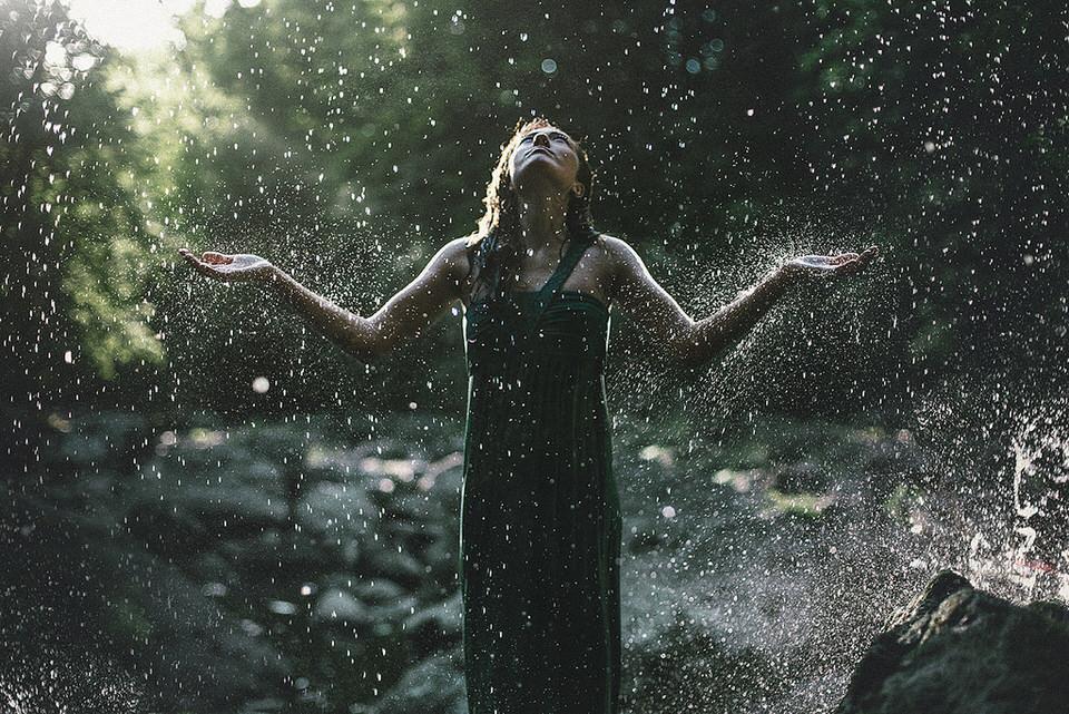 Eine Frau im Regen hält ihre Arme nach oben.