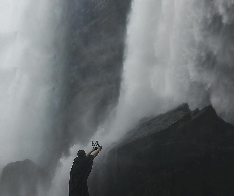 Eine Person hält ein Spielzeugschiff entgegen eines Wasserfalls.