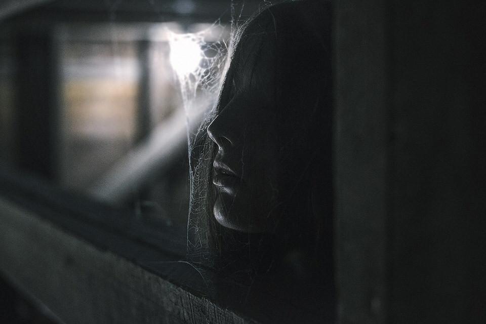 Eine Frau hält ihr Gesicht an ein Spinnennetz.