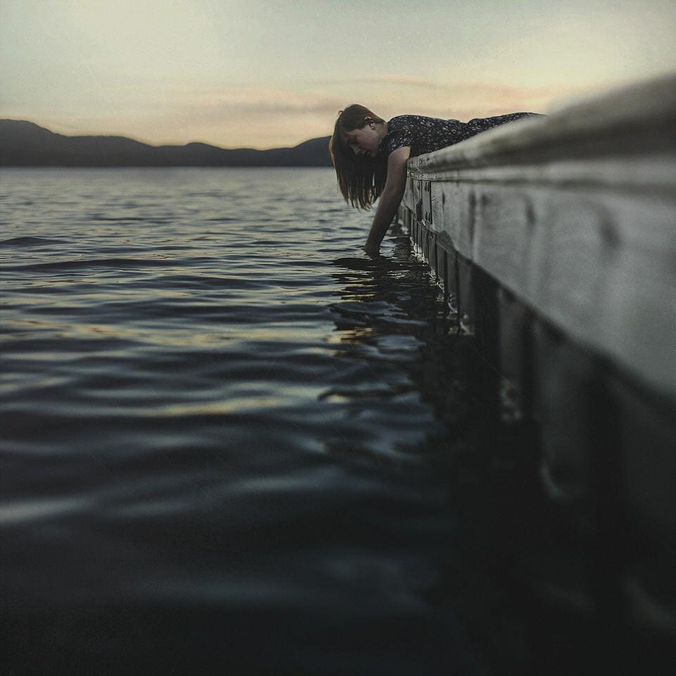 Eine Frau lehnt sich aus einem Boot und hält ihre Hand ins Wasser.