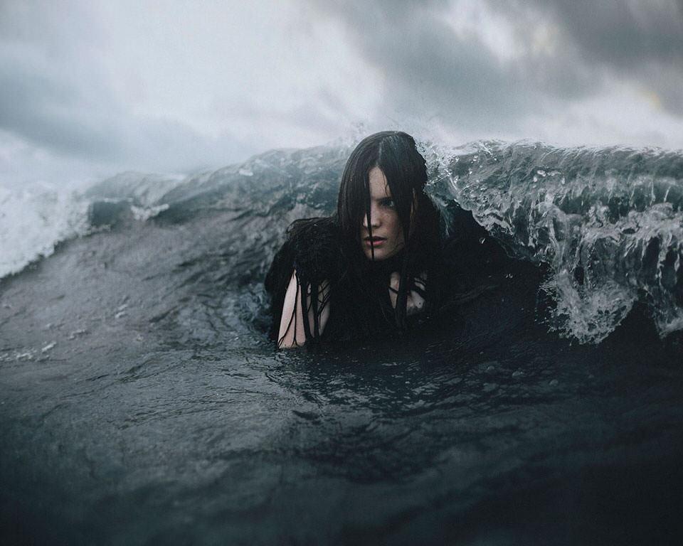 Eine Frau über die sich eine Welle bricht.